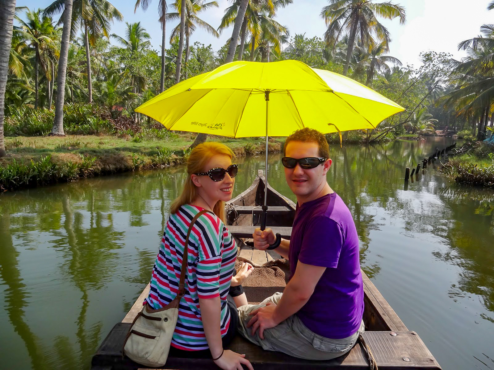 Rosie and Karl wearing sunglasses, under a yellow umbrella sitting on a wooden boat in the Kappil Backwaters, Kerala, India