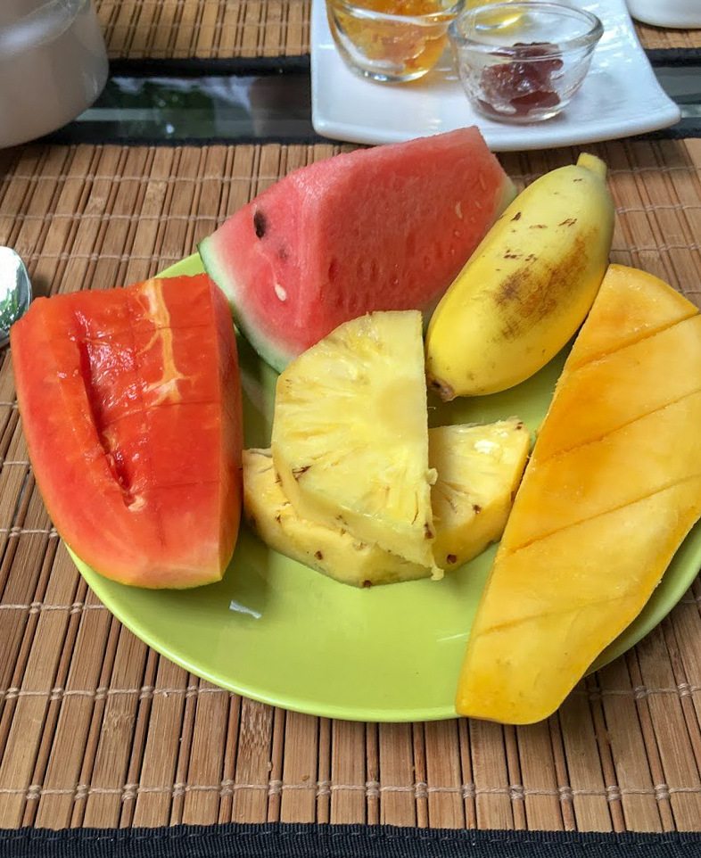 a green plate on a rattan mat with a banana, mango, melon and pineapple