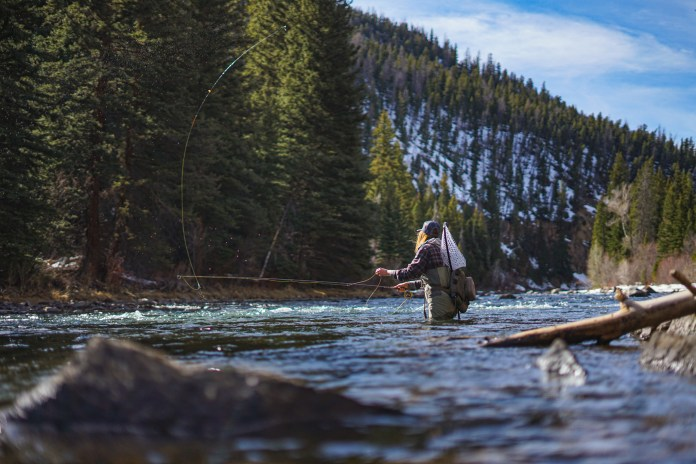 An angler casts a line on the banks of the Blue River, in Colorado
