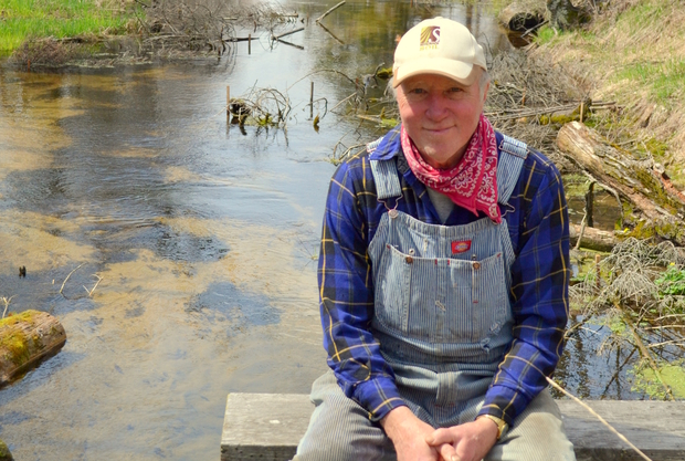 Donald Justin Isherwood sitting in front of the restored brook trout stream