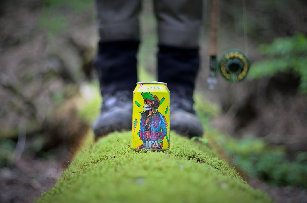 Voodoo Ranger beer and angler standing on a moss-covered log