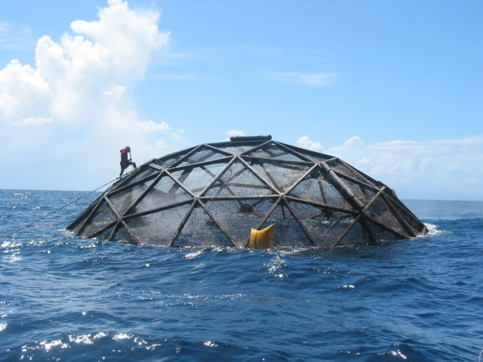Large metal fish cage floating in the ocean