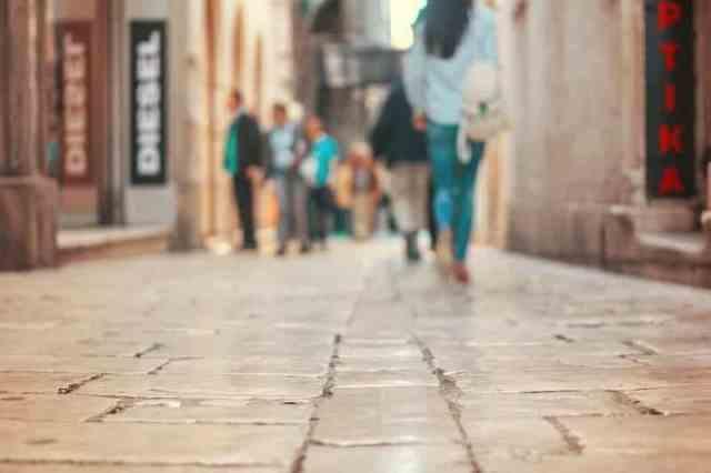 Melbourne shopping laneways. Lady in jeans walking down a cobblestone laneway with fashion boutiques.