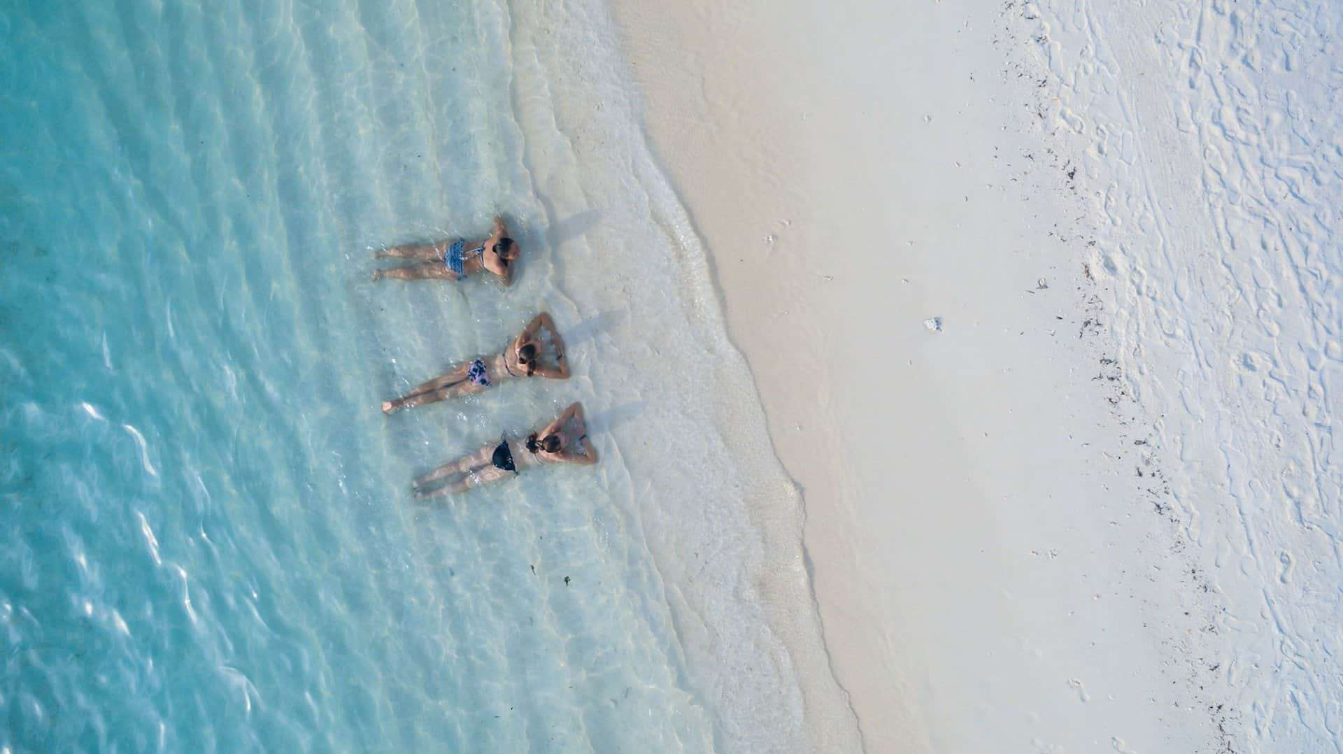 Girls lying on a beautiful white sandy beach with turquoise blue water.