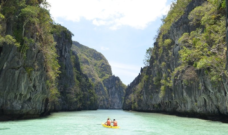 Couple in kayak in clear water between limestone cliffs in Philippines