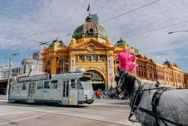 Flinders Street Station in Melbourne. A grand old building with a modern tram passing in front and horse and carriage.