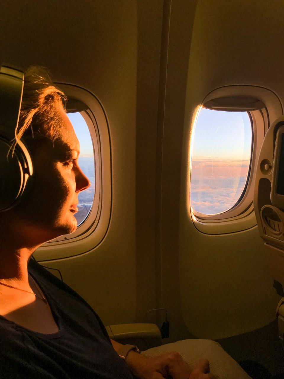 Woman on airplane at window seat with headphones
