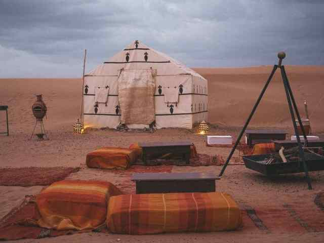 Sahara Desert glamping experience with white canvas tent and fire pit surrounded by Moroccan rugs and cushions.