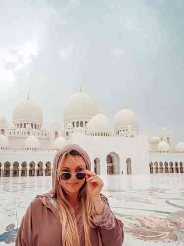 Girl in pink Abaya and sunglasses standing in the Abu Dhabi Grand Mosque mosaic tiled courtyard