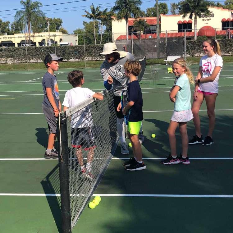 Tennis coach instructing group of children