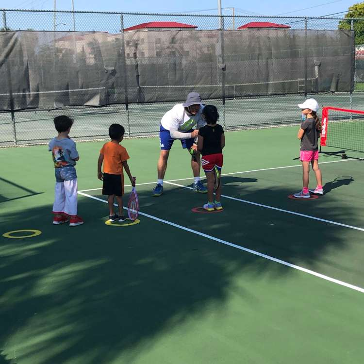 Young tennis players with coach at after school program
