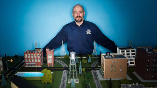 Ed Skoudis, a SANS Institute instructor, stands over a 1:87 scale miniaturized city used to teach U.S. Army and Air Force cyber warriors how to defend industrial control systems from cyber-attacks. The small city features real-world infrastructure systems, including electrical power distribution, as well as water, transit, hospital, bank, retail and residential infrastructures.