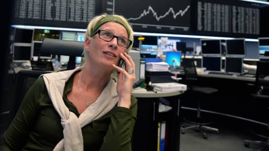A trader speaks on the phone in front of the index board in Frankfurt, Germany.