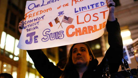 An American holds a sign as people gather for a vigil outside the Consulate General of France to pay tribute to the victims of an attack on satirical magazine Charlie Hebdo, in San Francisco.