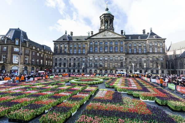 Leute besuchen niederländischen nationalen Tulip Day vor dem königlichen Palast am Verdammungs-Quadrat, in Amsterdam, die Niederlande.