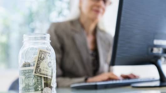 Businesswoman working, jar of money in foreground