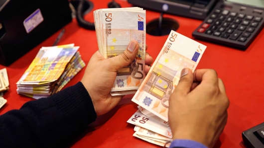 An employee counts fifty euro banknotes at his desk inside a Travelex store, operated by Travelex Holdings in London.