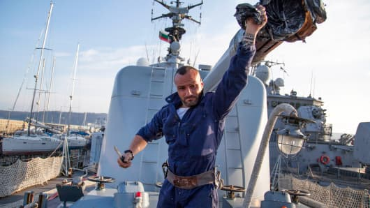 "An Italian sailor from the frigate ""Alieso"" removes a cover from a cannon in the Black Sea port of Varna, Bulgaria, March 9, 2015."