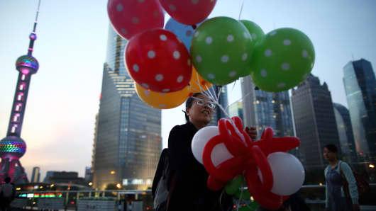 A woman holding balloons walks near Oriental Pearl Radio & TV Tower in Shanghai