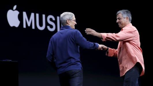 Apple CEO Tim Cook, left, greets senior vice president of internet services and software Eddy Cue.
