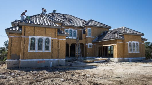 Construction workers add a roof to a new home in the Andalucia neighborhood of The Dominion gated community in San Antonio, Texas.