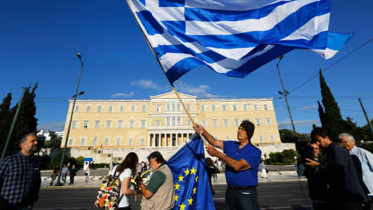 A protester waves a Greek flag in front of the parliament building during a rally in Athens, Greece, June 22, 2015.