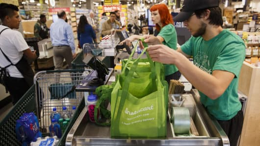 InstaCart employees fulfill orders for delivery at the new Whole Foods Market Inc. store in downtown Los Angeles, California.