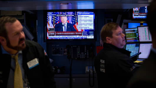 Traders at the New York Stock Exchange watch Donald Trump speaking on TV.