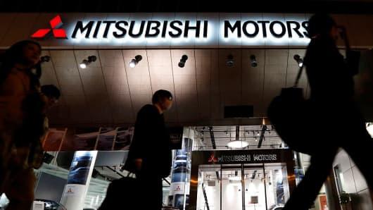 Pedestrians walk past the Mitsubishi Motors headquarters on April 20, 2016 in Tokyo, Japan.