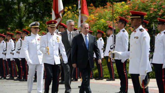 Israel's Prime Minister Benjamin Netanyahu (centre R) and his Singaporean counterpart Lee Hsien Loong (C) inspect the guard of honour during a welcoming ceremony at the Istana presidential palace in Singapore on February 20, 2017.