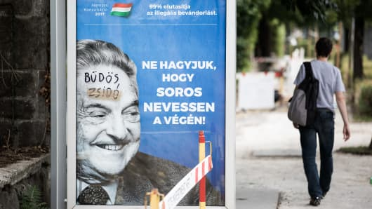 """Billboard campaign by the Hungarian government shows George Soros smiling next to the words """"Let's not let Soros have the last laugh."""" The graffiti translates to """"dirty Jew."""""""