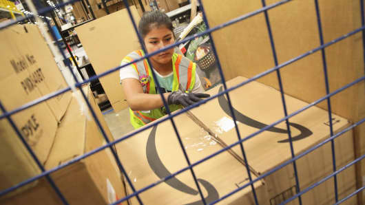 A worker packs customer orders at the Amazon fulfillment center in Romeoville, Illinois.