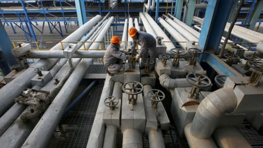 Employees close a valve of a pipe at a PetroChina refinery in Lanzhou, Gansu province.