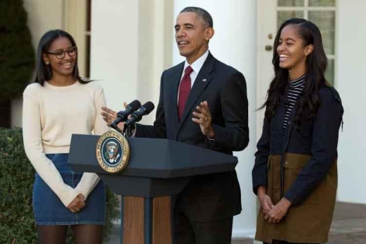 El presidente de Estados Unidos, Barack Obama, habla con sus hijas Sasha (L) y Malia durante la ceremonia anual de perdón del pavo en el Jardín de las Rosas en la Casa Blanca el 25 de noviembre de 2015 en Washington, DC