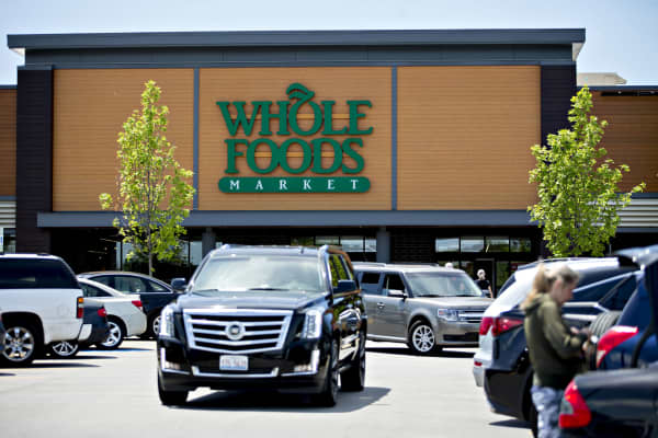Vehicles drive through the parking lot outside a Whole Foods Market Inc. location in Willowbrook, Illinois.