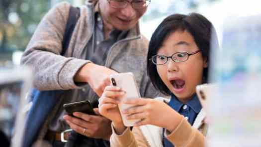 A girl reacts as she tries an iPhone X at the Apple Omotesando store on November 3, 2017 in Tokyo, Japan.