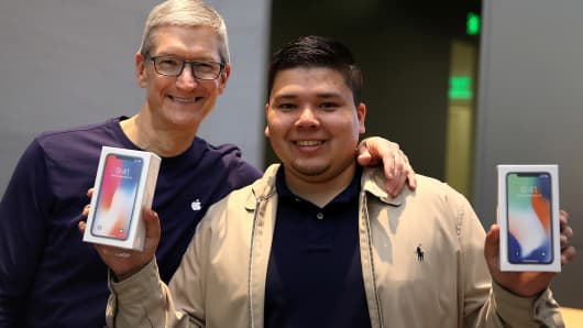 Apple CEO Tim Cook (L) takes a picture with David Casarez (R) who just purchased the new iPhone X at an Apple Store on November 3, 2017 in Palo Alto, California.