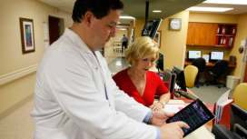 A doctor demonstrates an app on an iPad to review medical tests of one of his patients at Northwest Medical Center in Margate, Florida.