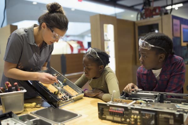 Scientist teaching twin sisters assembling electronics in science center