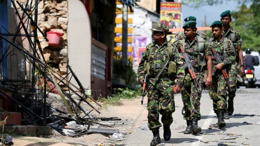 Sri Lanka's Special Task Force soldiers walk past a damaged houses after a clash between two communities in Digana central district of Kandy, Sri Lanka March 8, 2018.