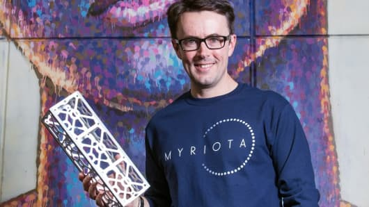 Co-founder and CEO of Myriota Alex Grant with a nanosatellite frame.