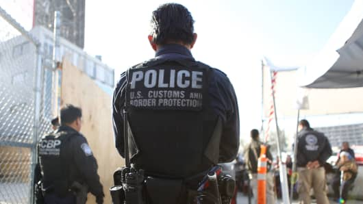 A U.S. Customs and Border Protection officer stands guard as pedestrians enter the United States at the San Ysidro port of entry on April 9, 2018 in San Ysidro, California.