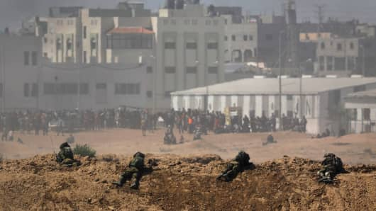 Smoke rises as Israeli soldiers are seen on the Israeli side of the border with the Gaza Strip, Israel.