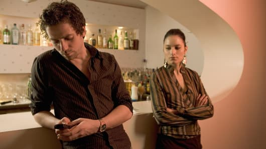 Man leaning against bar counter text messaging while woman is standing alone with arms crossed