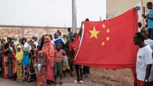 Djiboutian people hold China's national flag before the launching ceremony of a new housing contruction project in Djibouti, on July 4, 2018. The new project is financially supported by China Merchants Group.