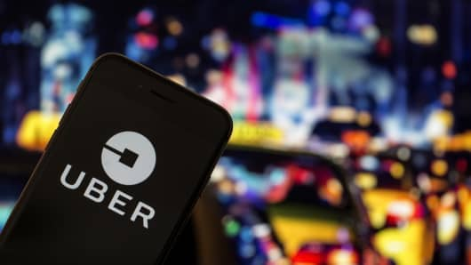Uber application logo is seen on a screen in front of taxi board in Ankara, Turkey on August 31, 2018.