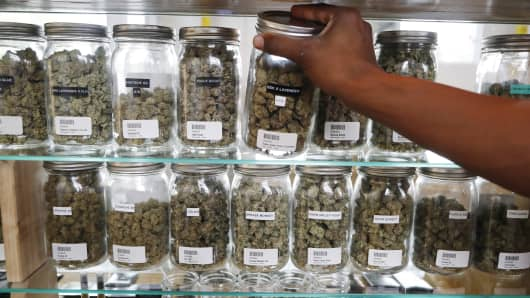In this Tuesday, Oct. 2, 2018, photo, a clerk reaches for a container of marijuana buds for a customer at Utopia Gardens, a medical marijuana dispensary, in Detroit.