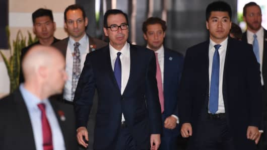 US Treasury Secretary Steven Mnuchin (C) is leaving the hotel with his negotiating team on the way to high-level trade talks in Beijing on February 14, 2019.