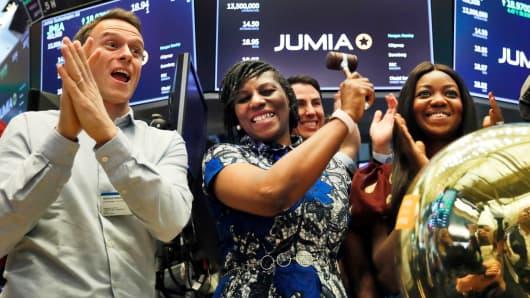 El co-CEO de Jumia, Sacha Poignonnec, a la izquierda, aplaude cuando la CEO de Jumia Nigeria, Juliet Anammah, centro, hace sonar una campana ceremonial cuando las acciones de la compañía comienzan a cotizar, en el piso de la Bolsa de Nueva York, el viernes 12 de abril de 2019.