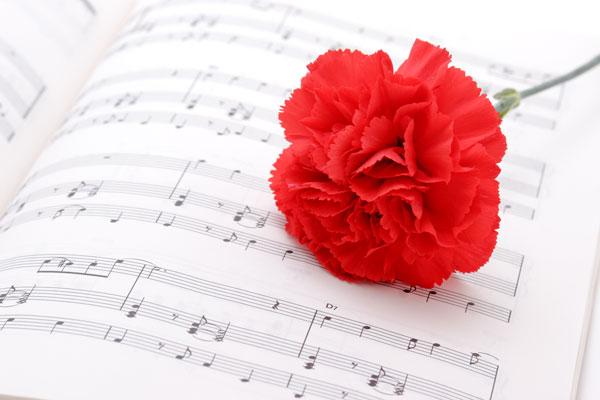 楽譜の上に置かれた一輪の赤いカーネーション